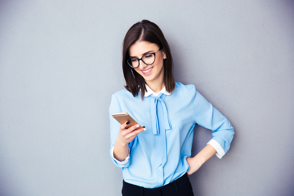 Smiling businesswoman using smartphone over gray background. Wearing in blue shirt and glasses.